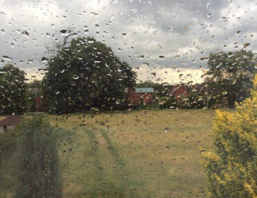 A village scene through a rainy window