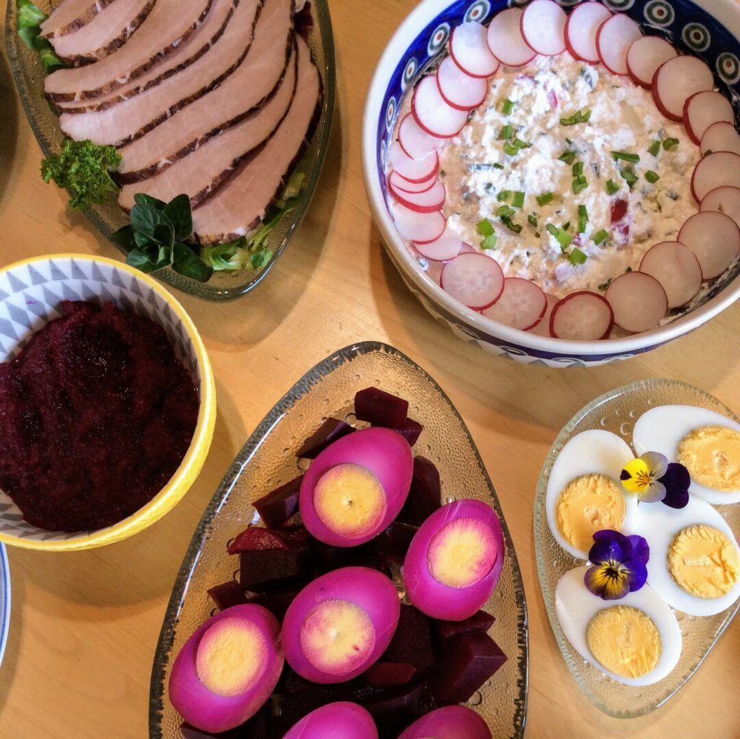A plate of slice meat, a bowl of radish and cheese salad, a plate of hard-boiled eggs, a plate of pickled eggs, a bowl of beet and horseradish relish for Easter.