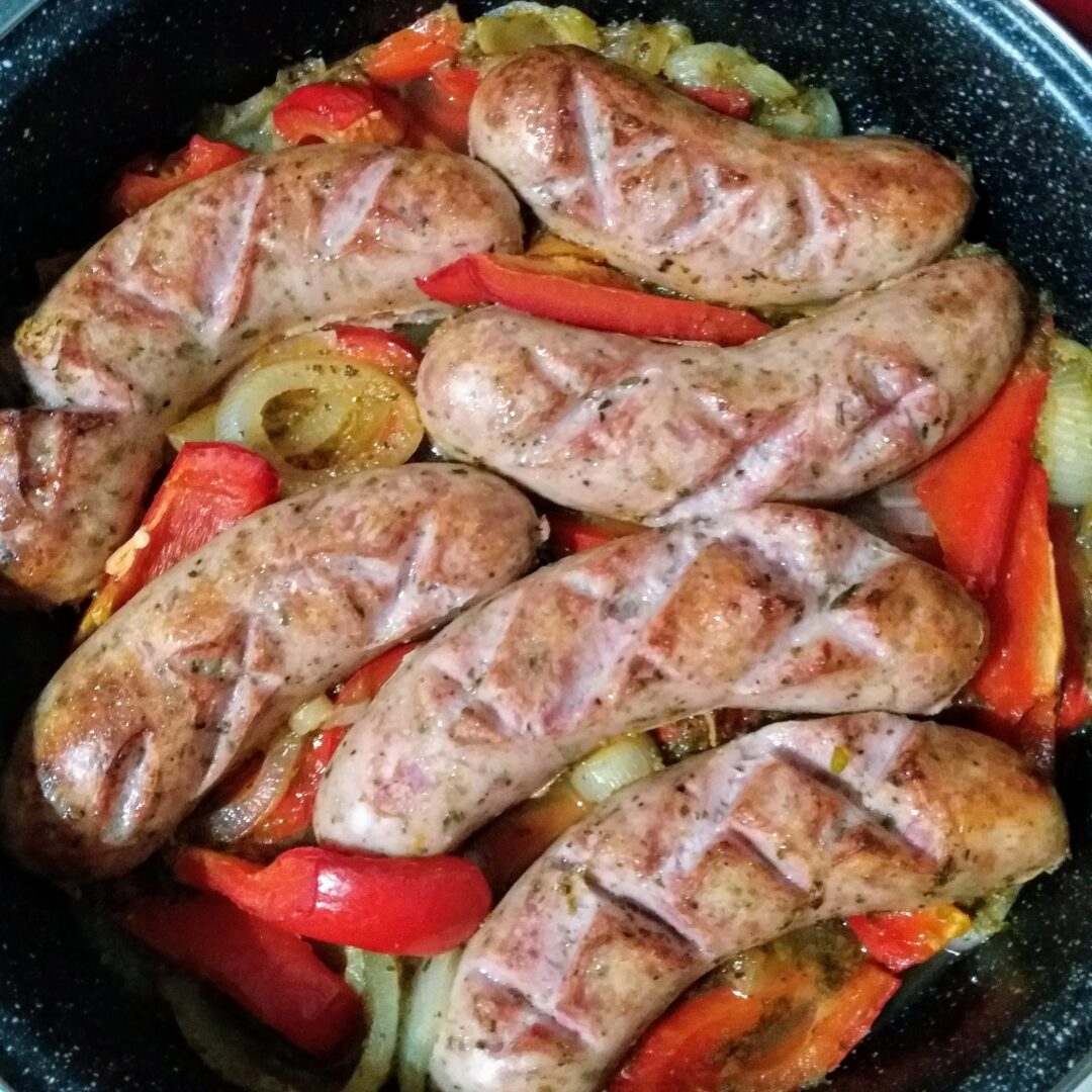 A pan of scored, white sausages with onion and red bell peppers.