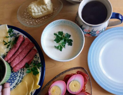 A plate of cheese and meat with a bowl of horseradish sauce, pickled eggs, a cup of tea, and a butter lamb.
