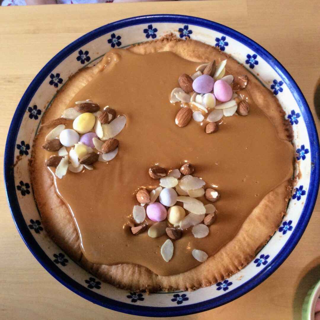 Round Polish Mazurek Easter cake decorated with caramel, almonds, chocolate eggs.