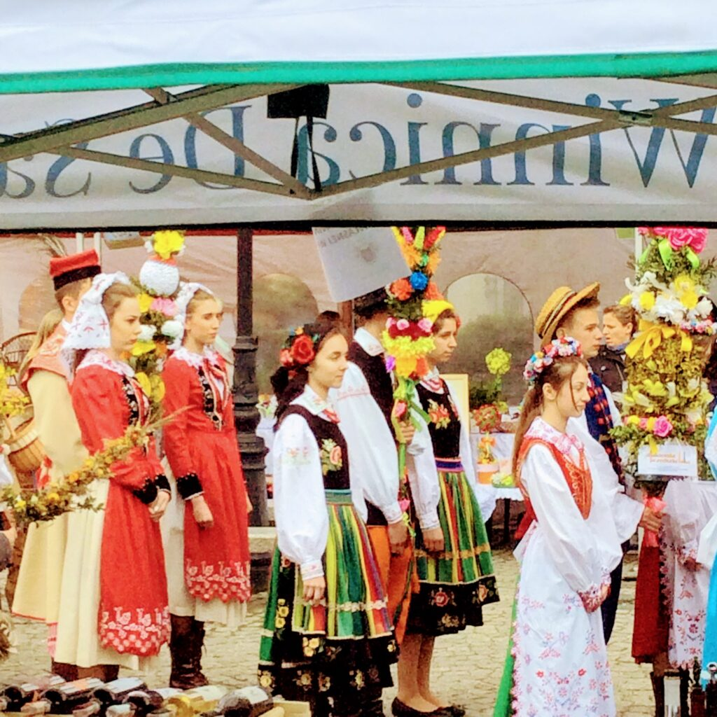 A line of young people in Polish national costume present palms for Palm Sunday palm contest