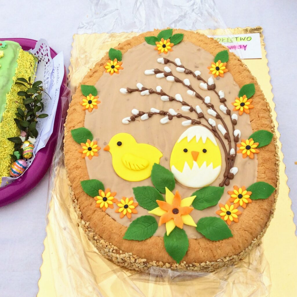 Egg-shaped Easter cake with chicks and pussy willow decorations