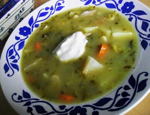 A white soup bowl with a blue design on the brim with Polish pickle soup and a dollop of sour cream