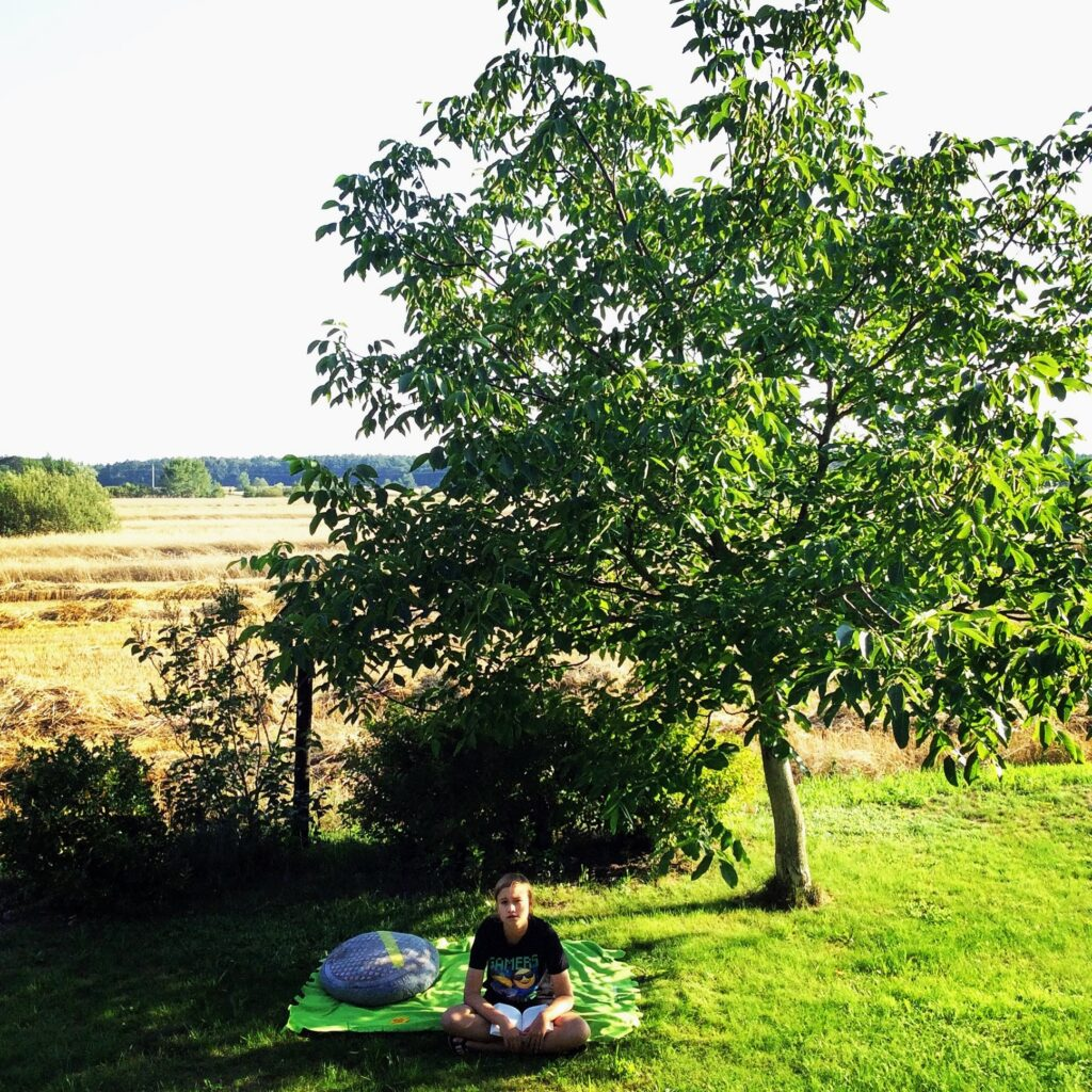 A child sitting on a blanket in the grass under a tree in a Polish village garden