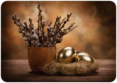 A vase of pussy willows next to two gold colored Easter eggs