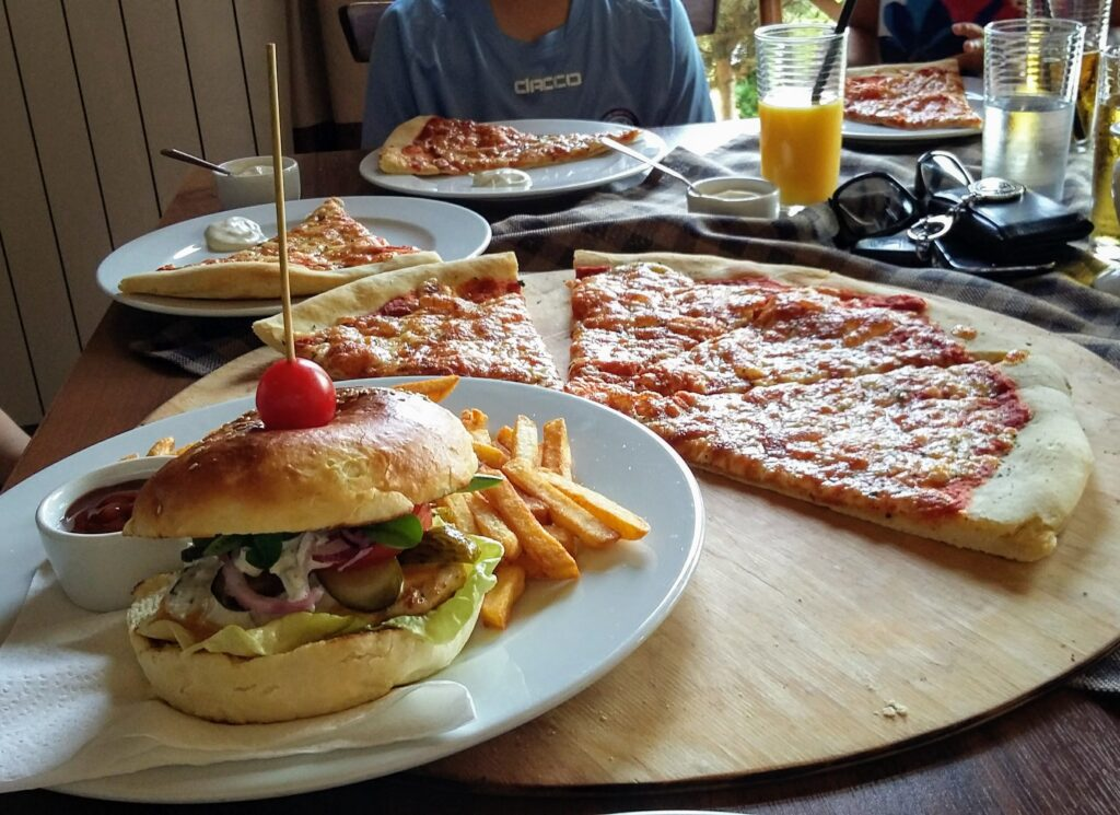 Table at a restaurant with a plate with burger and fries and a partially eaten pizza on a wooden pizza block