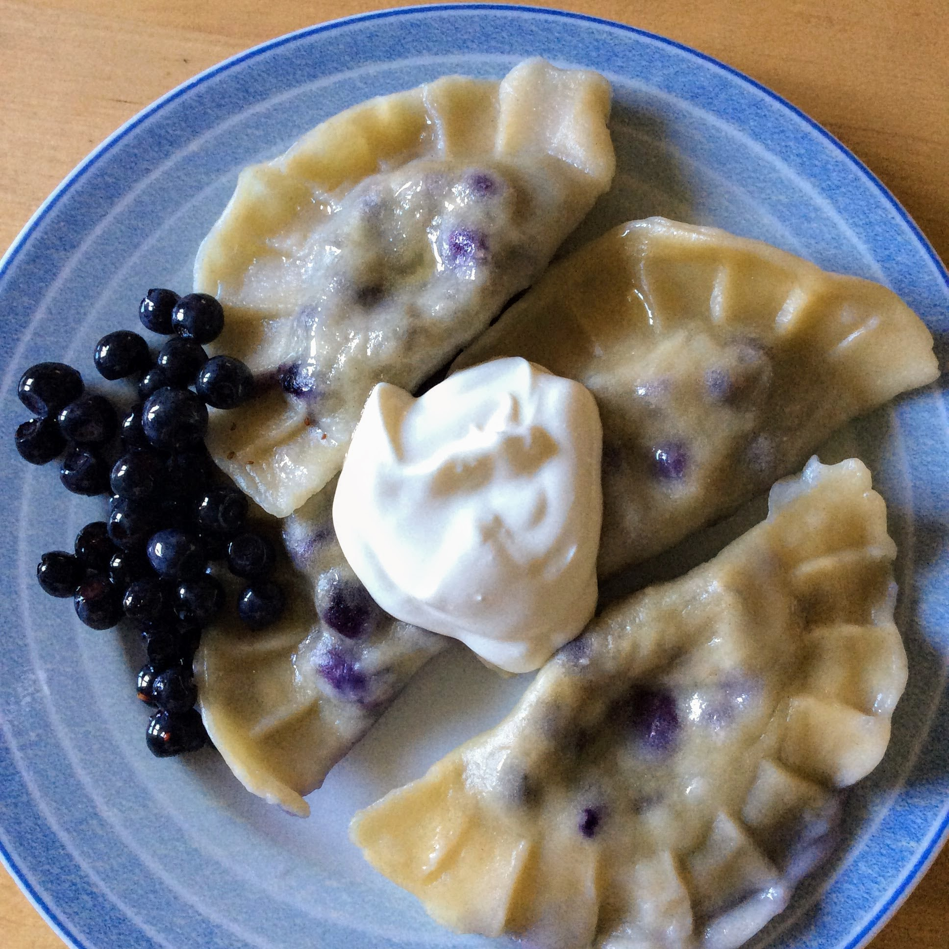 Plate of blueberry pierogi with a dollop of cream in the middle and blueberries on the left side